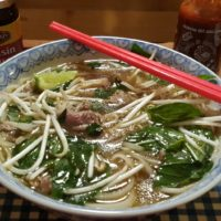 A patterned bowl with Pressure Cooker Vietnamese Pho Bo Tai in it and two red chopsticks.