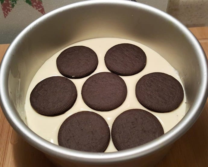 A close up of cake pan with batter and cookies