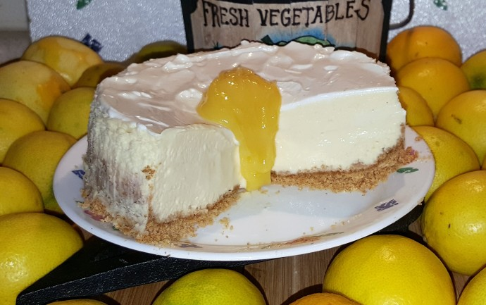 A close up of Pressure Cooker Meyer Lemon Cheesecake on a cake plate with loose lemons next to it and in a fruit bowl.