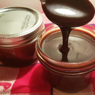 A mason jar with a spoon pouring the Hot Fudge Sauce