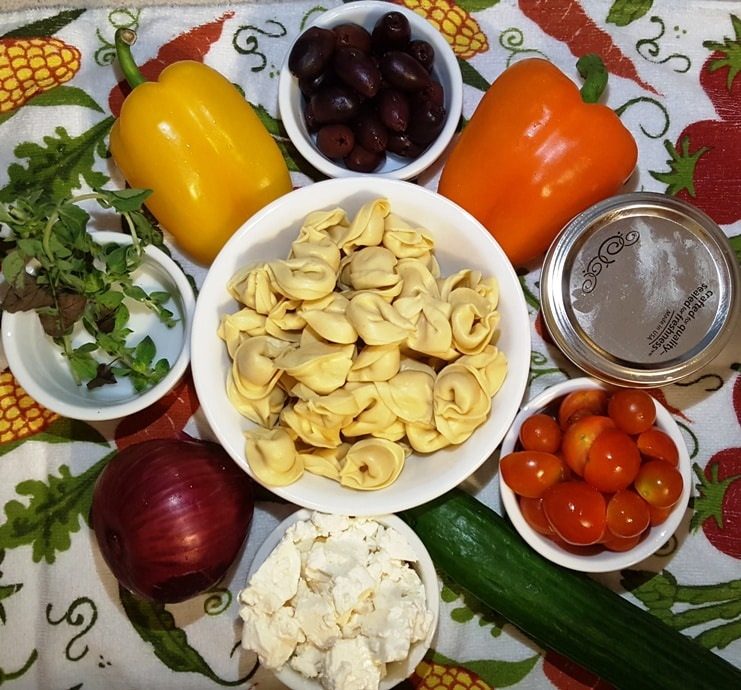 A close up of the ingredients for a tortellini salad