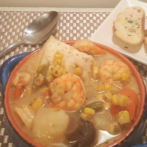 Blue bowl with shrimp, scallows, corn, green means, carrots in a creamy broth Instant Pot Seafood Corn Chowder