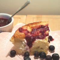 A portion of blintz souffle on a plate with sauce and blueberries