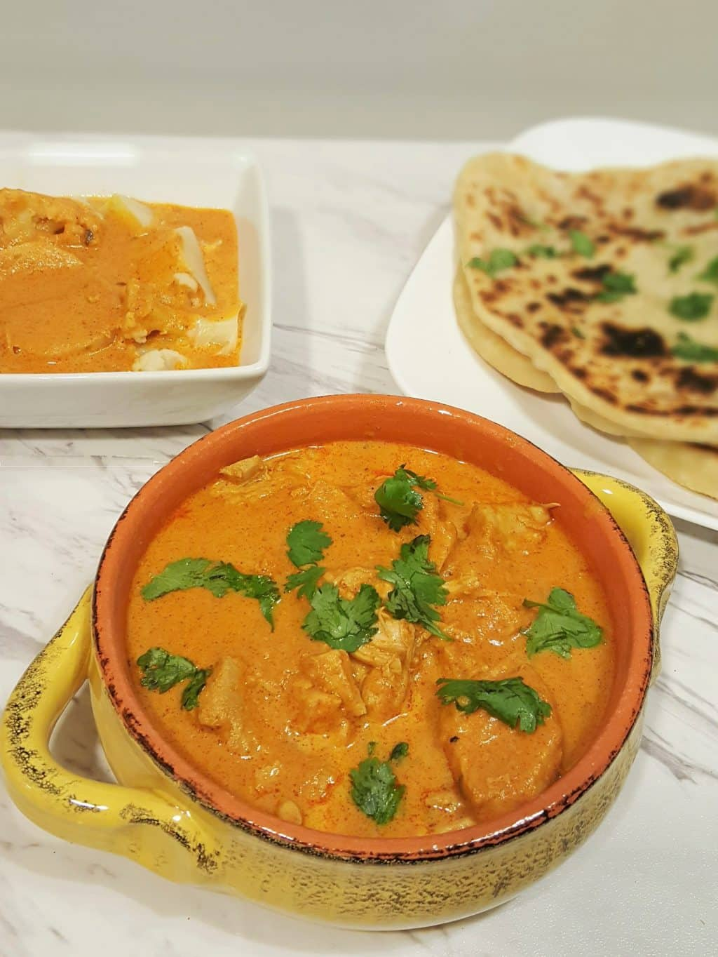 A bowl of Indian butter chicken on a plate with indian flatbread on another plate.