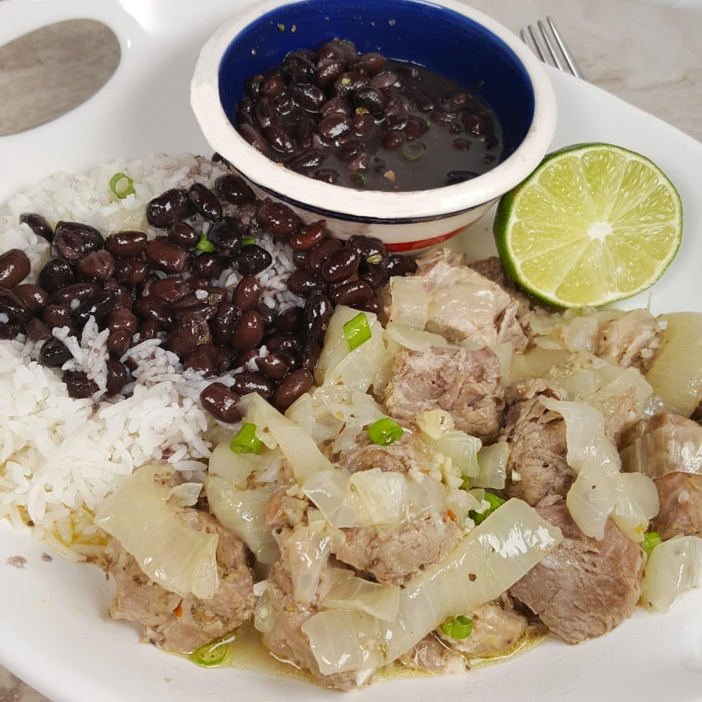 A white serving plate of Pressure Cooker Lechón Asado {Cuban Pork with Mojo} with rice, half a lime, and a bowl of black beans in a colorful round bowl.