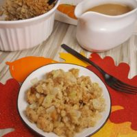 A round plate with stuffing in it and a white jug with gravy in it.