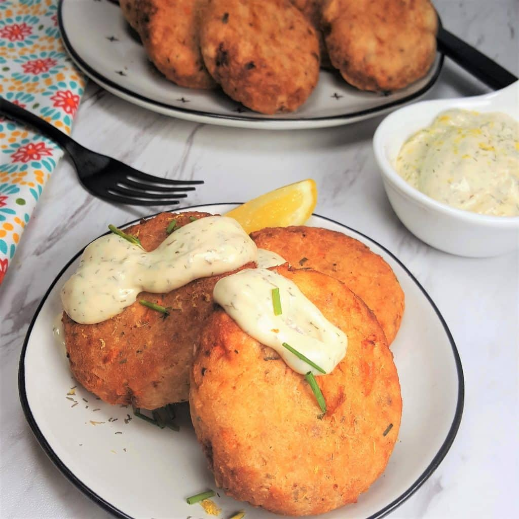 A round plate with three Air Fryer Salmon Croquettes in it, a slice of lemon, and a dollop of Lemon Dill Aioli.