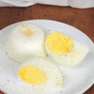 Instant Pot No Peel Hard Boiled Eggs on a while plate with one egg cut in half