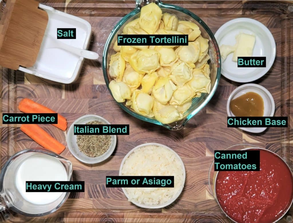 Cast of Ingredients for Instant Pot Tomato Tortellini Soup - pictures of all ingredients in bowls on a wooden cutting board.