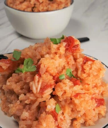 Pressure Cooker Jollof Rice on a white plate with a black fork