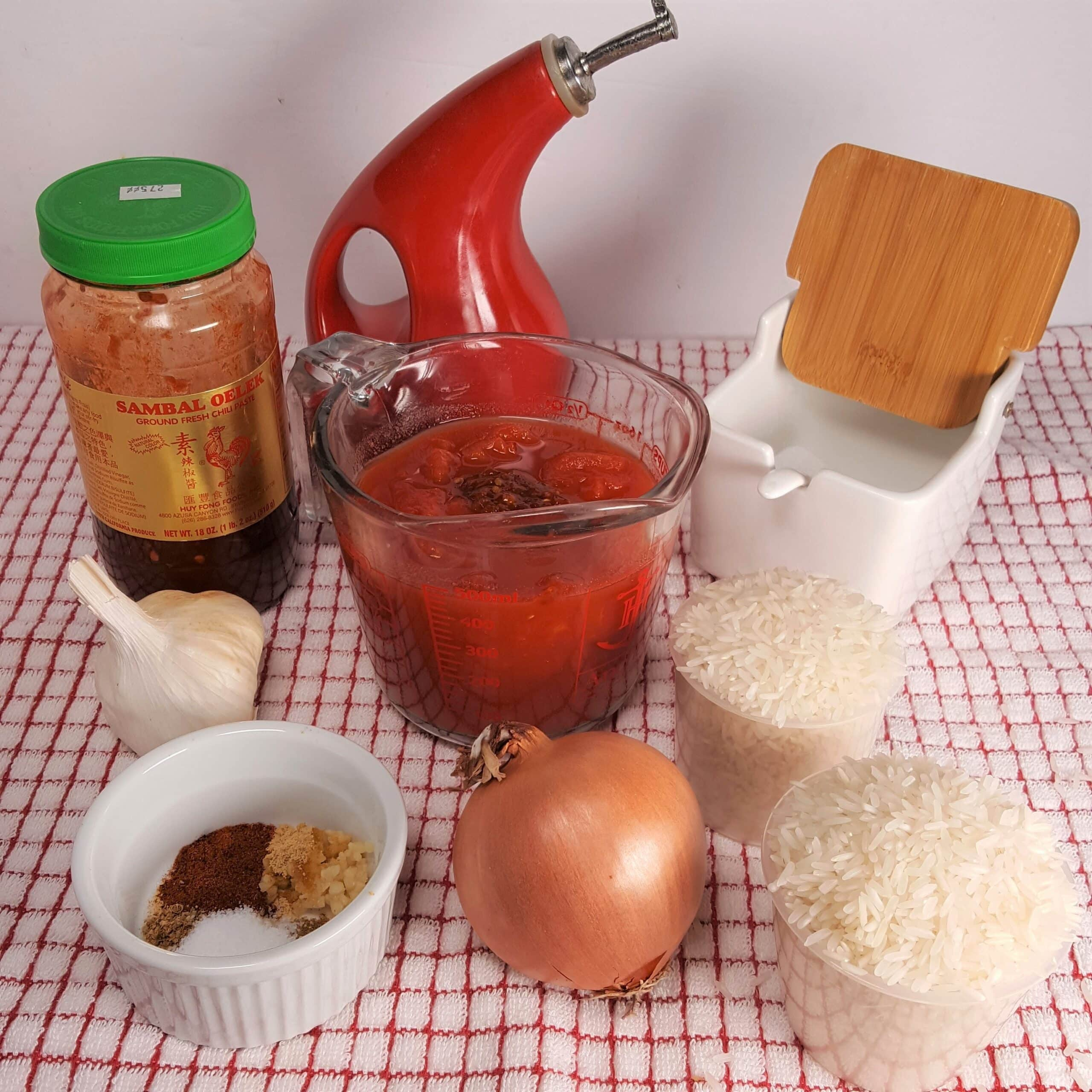 Cast of Ingredients for Pressure Cooker Jollof Rice - Sambal Oelek, Oil, Rice, Garlic, Onion, Tomato Sauce, Salt, Ginger on a red and white checked mat
