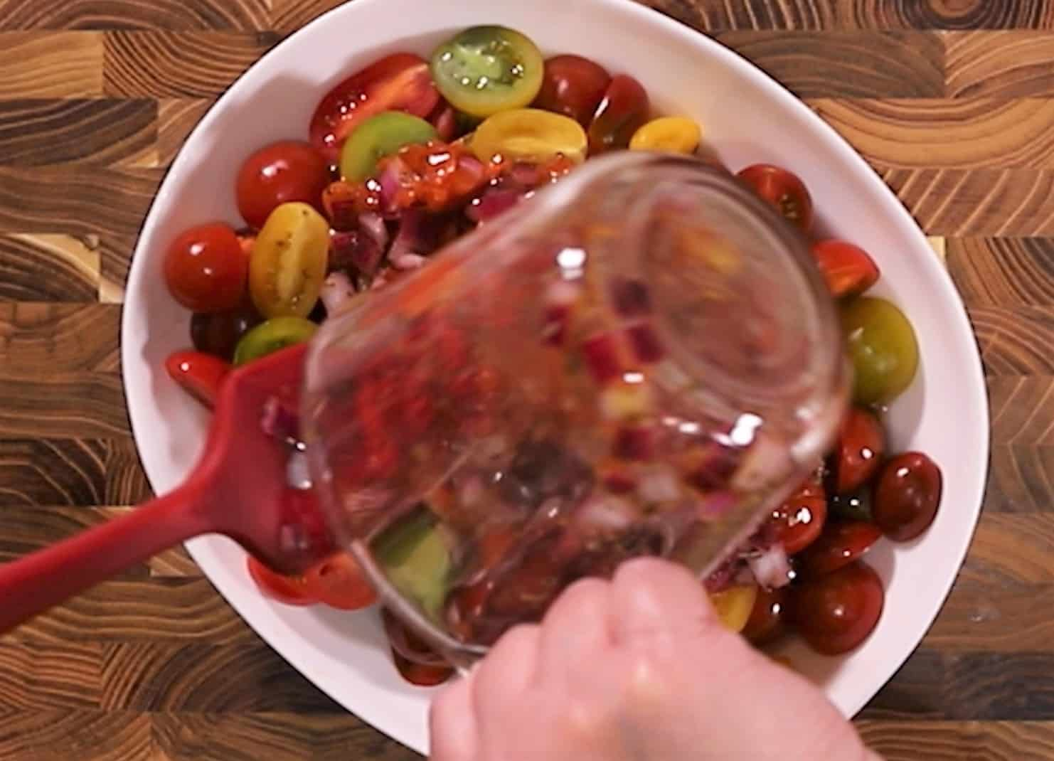 Sliced tomatoes in white serving dish with a glass measuring cup pouring marinade over the tomatoes.