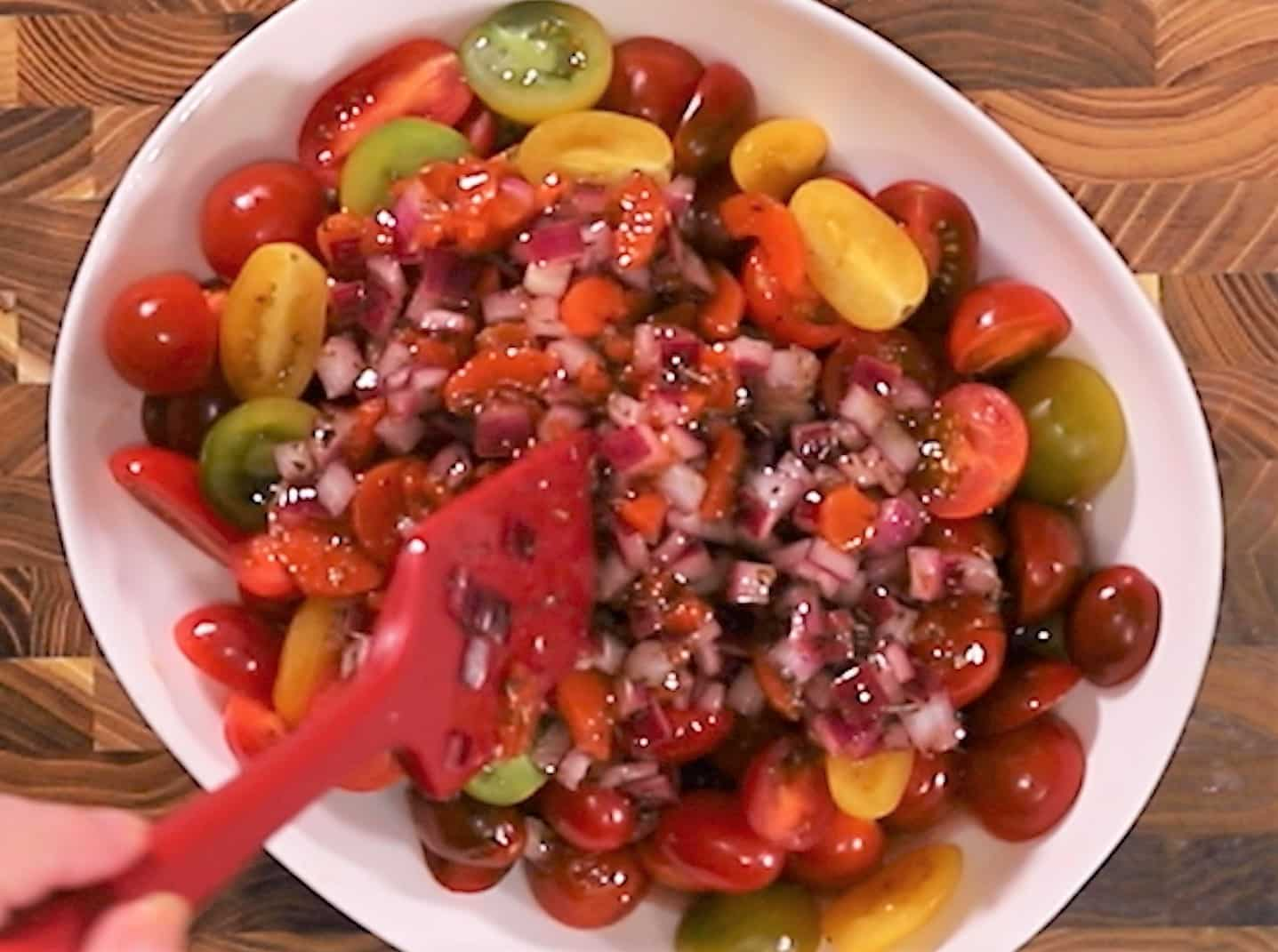 White serving platter with the marinade being mixed into the sliced tomatoes.