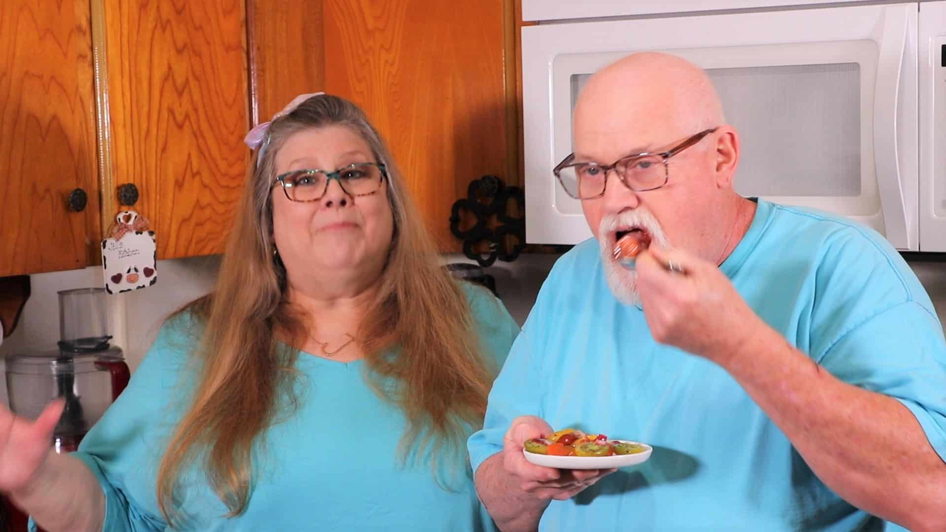 Jill and Ed wearing blue shirts standing in front of microwave in kitchen holding a plate of tomato salad and Ed is using a fork to have a taste.