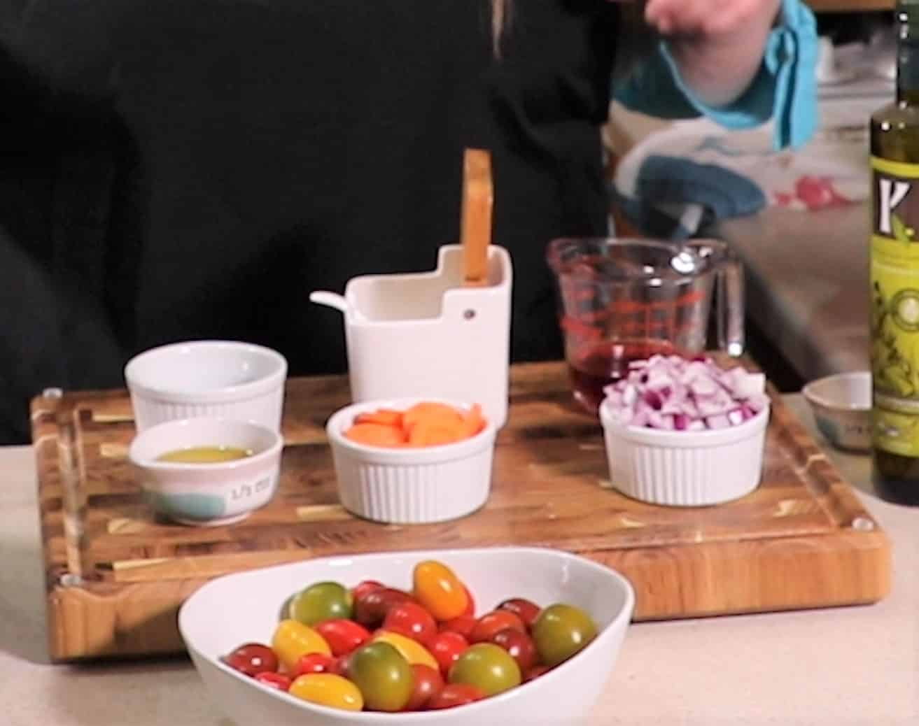 Ingredients for Fresh Tomato Salad recipe on teak wood cutting board containing tomatoes, sliced carrots, onions, Italian seasoning, red wine vinegar, olive oil and sugar