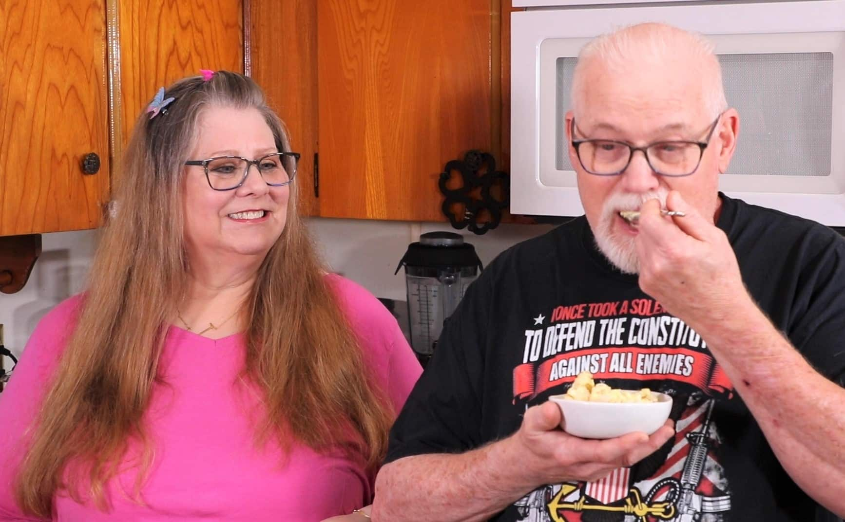 Jill wearing a pink shirt and Ed wearing a black shirt. Ed is holding a small bowl of cauliflower salad and using a fork to taste.