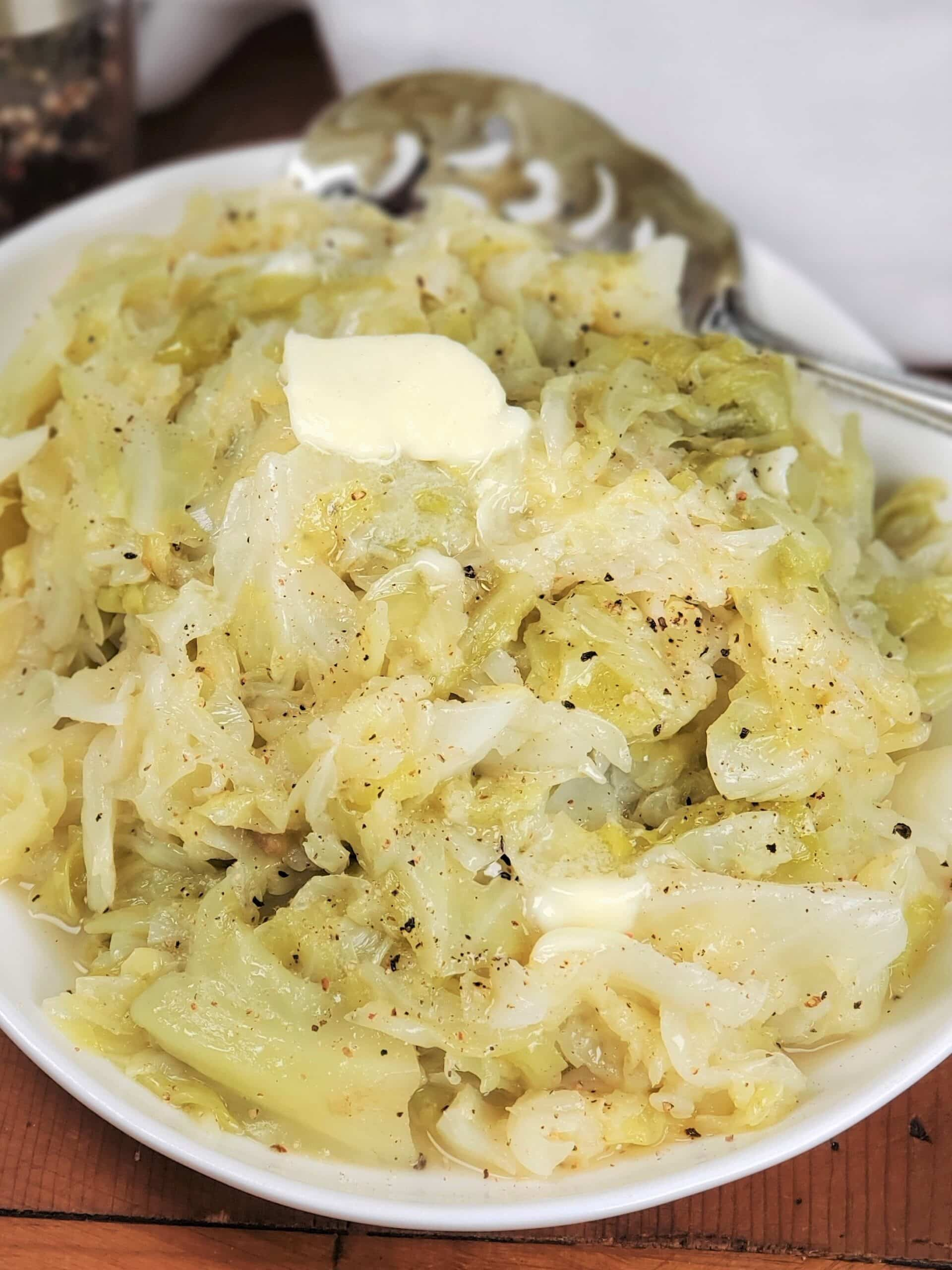 A white bowl with Instant Pot Buttered Cabbage and a spoon ready to serve