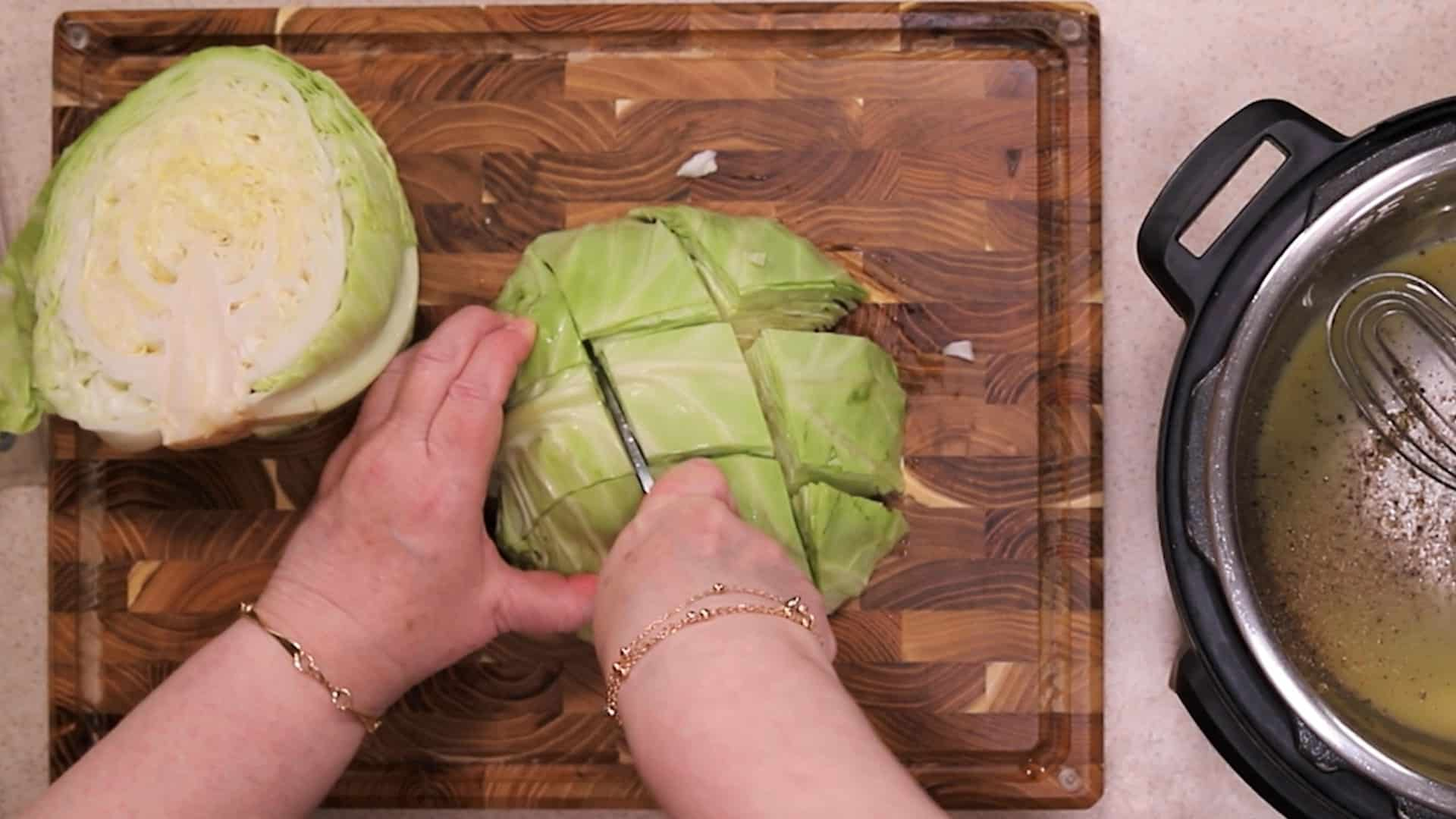 Brown cutting board with head of cabbage and being chopped with a chef's knife