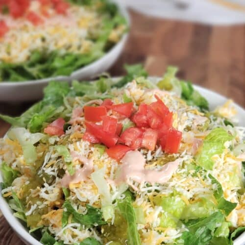 White bowl with ground beef, lettuce, cheese, pickles, tomatoes, thousand island dressing