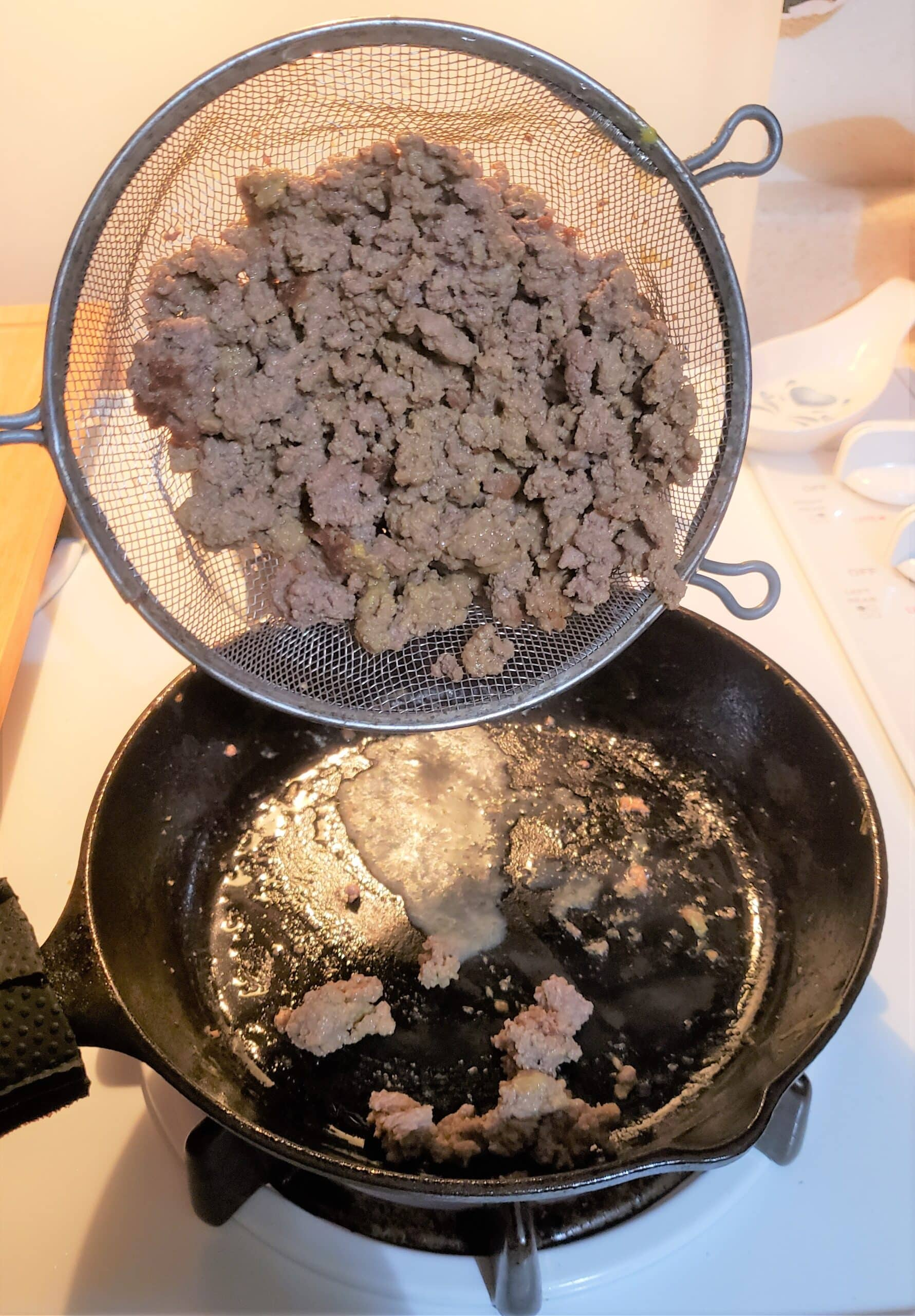 Ground beef in strainer being poured into a hot skillet