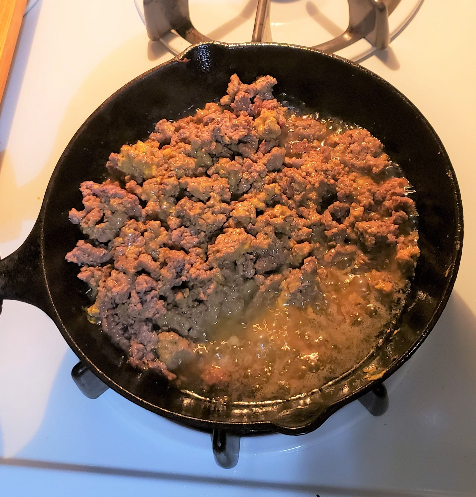 Cast iron skillet with ground beef showing all the grease